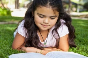 Hispanic girl laying in grass reading book